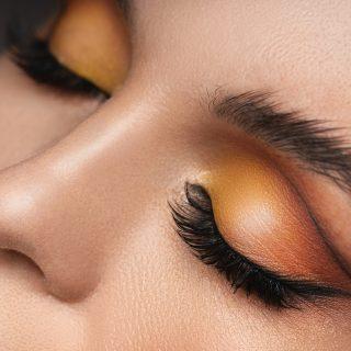 Closeup of female eyes with a colorful eyeshadow and eyebrow lamination